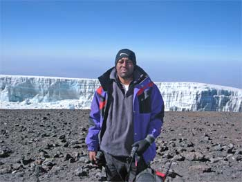 Kwameh at Uhuru Peak with the Southern Icefields in the background.
