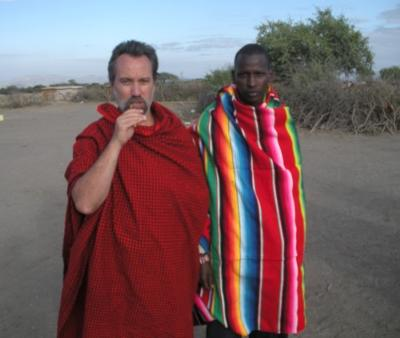 Me with one of  the Maasai warriors in the morning before we left. The stick I'm chewing on is their idea of a toothbrush. You can see their brush fence in the background.