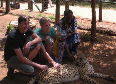 2 young friends with Maasai girl petting Cheetah